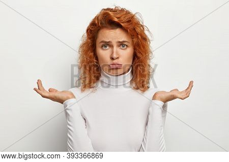 Sad Gloomy Redhead Woman Purses Lower Lip, Makes Serious Decision, Feels Doubt And Uncertainty, Spre