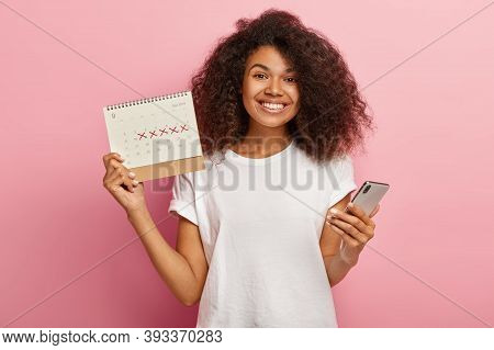Happy Curly Woman Holds Periods Calendar, Checks Menstruation Days On Mobile Phone Application, Care