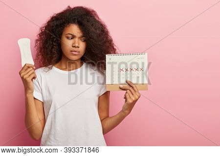 Photo Of Discontent Lovely Curly Haired Woman Looks At Calendar With Marked Pms Days, Holds Sanitary