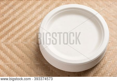 Stack Of Biodegradable, Compostable Or Eco Friendly Disposable Plate On Woven Bamboo Background, Sus