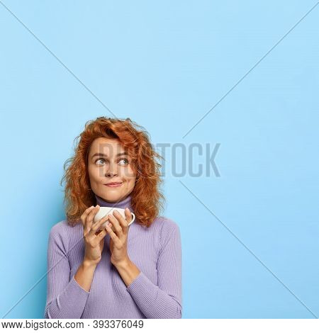 Coffee Break Concept. Beautiful Thoughtful Redhead Woman Holds Mug Of Espresso, Enjoys Spare Time An