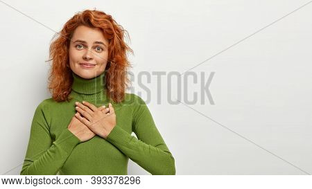 Satisfied Pleased Redhead Green Eyed Woman Keeps Hands On Chest, Feels Thankful And Grateful, Expres