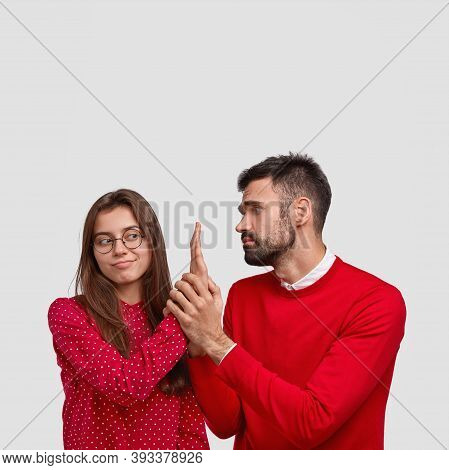 Begging Unshaven Handsome Man In Red Sweater Looks With Miserable Expression At Girlfriend, Asks For