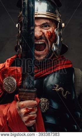 Armoured And Savage Greece Warrior With Red Mantle And Helmet Screams Holding His Gladius In Dark Ba