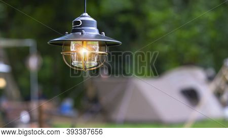 Focus At Vintage Black Camping Lantern With Blurred Background Of Tents In Camping Area At Natural P