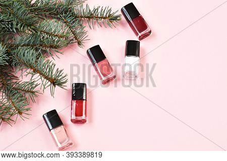 Nail Polishes With Fir Branches On A Pink Background. Manicure Concept. Manicure Product Set With Ch