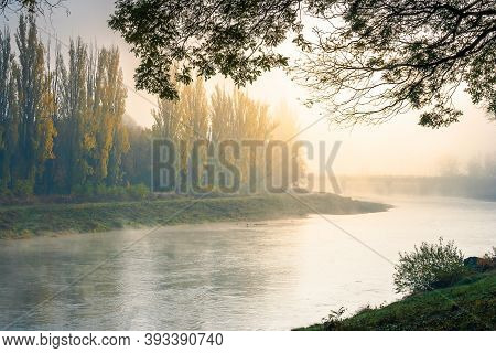 Misty Morning Sunrise On The River. Beautiful Autumnal Scenery With Glowing Sky. Bridge In The Dista