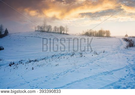 Foggy Countryside At Dawn. Beautiful Rural Landscape In Wintertime. Trees On Snow Covered Hills Bene