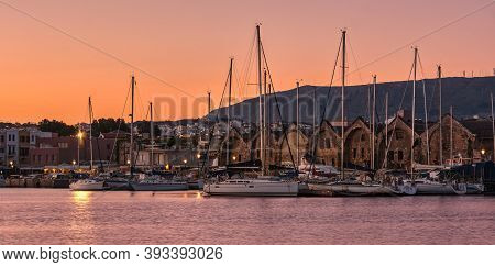 Sunrise Over Old Venetian Port And Harbour Of Chania, Crete, Greece. Sailing Boats, Pier, Old Veneti