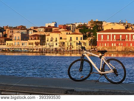 Sunrise In Old Venetian Port, Chania, Crete, Greece. Pier, Bicycle, Quayside, Maritime Museum. Bike