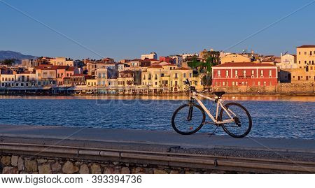 Early Morning In Old Venetian Harbour Of Chania, Crete, Greece. Pier And Bicycle, Jetty And Quayside