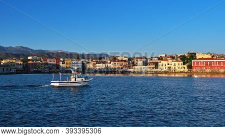 White Fishing Boat Passing By Old Venetian Harbour Quay And Maritime Museum In Chania, Crete, Greece