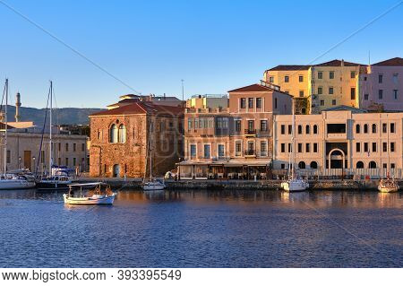 Fishing Boat Pass By Grand Arsenal In Old Venetian Harbour, Chania, Crete, Greece. Sunrise View Of Q