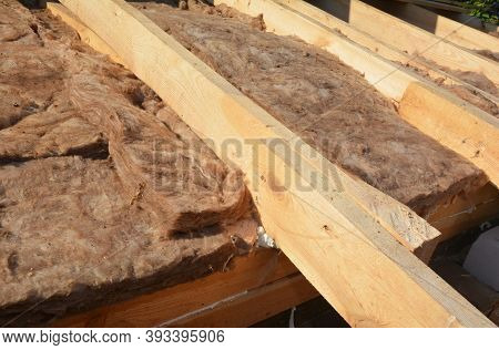 A Close-up On An Exterior Roof, Loft Or Attic Insulation With Glass Mineral Wool Between The Wooden