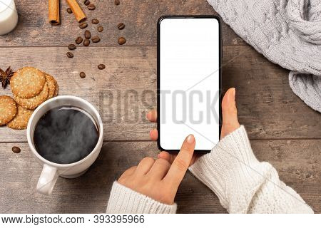 Mobile Phone Mockup In A Cafe In Winter. Mockup Image Of Woman's Hands Holding Cellphone With Blank
