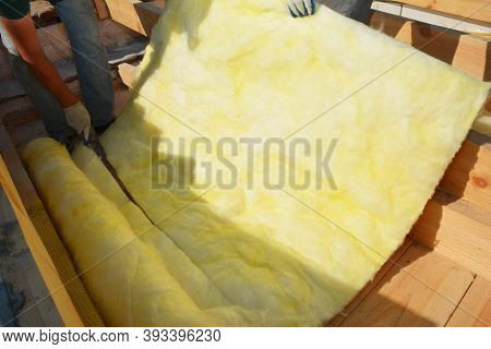 A Building Contractor Is Unrolling Glass Wool Batt Or Blanket, And Is Cutting A Sheet For The Roof I