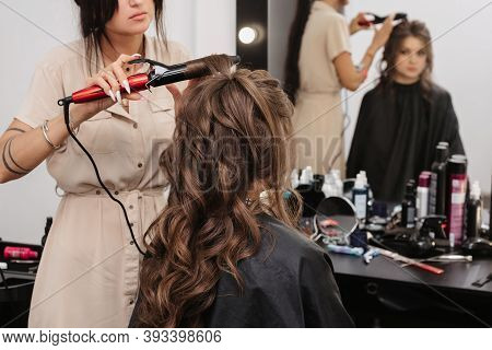 Stylist Makes Curls Curling Girl With Long Brown Hair
