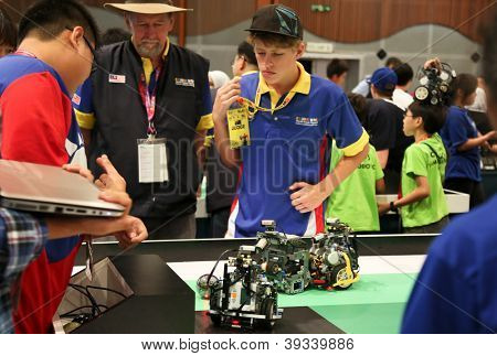 SUBANG JAYA - NOV 10: Unidentified students watch their robots with built in programmed response compete in a football match at the World Robot Olympaid on Nov 10, 2012 in Subang Jaya, Malaysia.