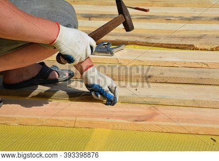 A Roofing Contractor Is Installing Wooden Sheathing, Deck, Planks On A Vapor Barrier Membrane Using