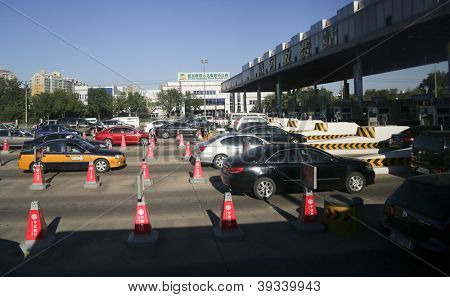 BEIJING - OCTOBER 13: Vehicles line up at the toll both of a highway on October 13, 2012 in Beijing, China. Beijing, a city of 22 million people has 5 million cars and 2,000 cars are added each month.
