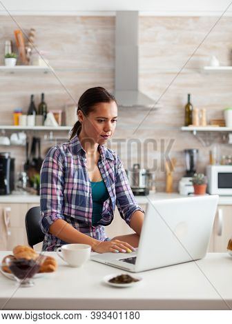 Lady Browsing On Internet Using Laptop In Kitchen And Having A Cup Of Hot Green During Breakfast. Wo
