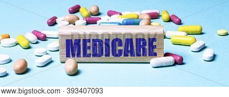 A Wooden Block With The Word Medicare Stands On A Blue Background Among Multi-colored Pills. Medical