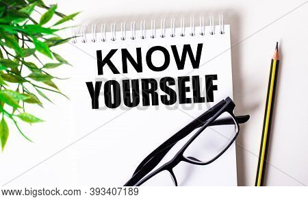 Know Yourself Is Written In A White Notebook Next To A Pencil, Black-framed Glasses And A Green Plan