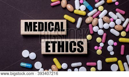 Medical Ethics Is Written On Wooden Blocks Near Multi-colored Pills. Medical Concept
