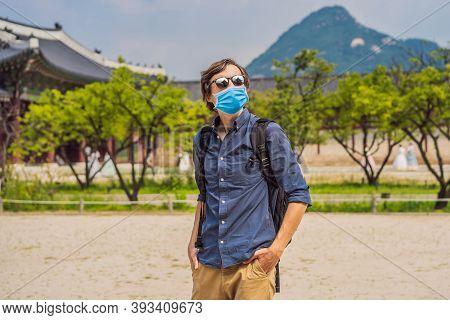 Man Tourist Wearing A Medical Mask During Covid-19 Coronavirus In Korea. Gyeongbokgung Palace Ground