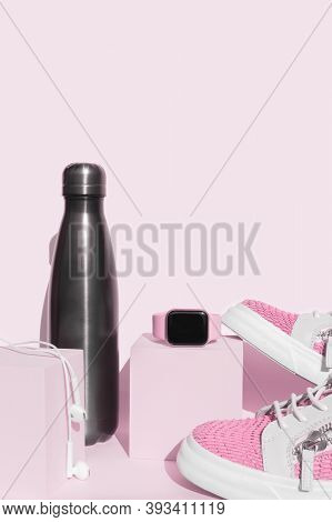 Modern Fitness Accessories Composition Reusable Water Bottle, Earphones And Smart Watch On Cube Plat
