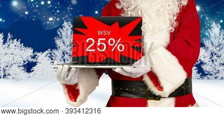 Santa Claus Holds Laptop In Hand With 25 Percent Winter Sale Advertising On Wintery Background