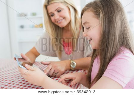 Mother and child holding a tablet computer at the kitchen