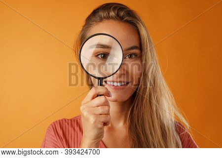 Beautiful Young Blonde Woman Looking On You Through Magnifying Glass