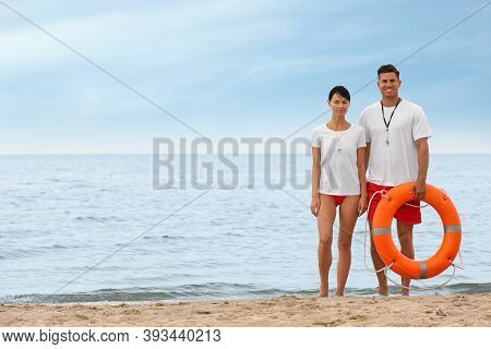 Professional Lifeguards With Life Buoy At Sandy Beach