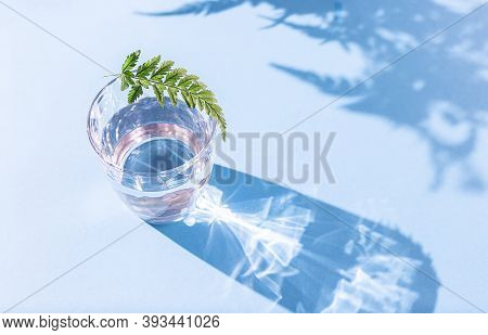 Glass Of Clean Transparent Water On A Light Background In Natural Light With Harsh Shadows.