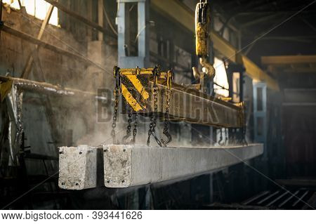 The Crane Moves A Reinforced Concrete Product With Holes. Reinforced Concrete Pillars Fixed With Met