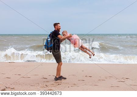 Father Holds His Cute Daughter In Arms, Circles Around Himself, Play Have Fun Together On Sea Beach.