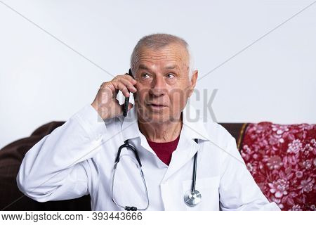 The Old Doctor Is Wearing A Headset And Talking On The Phone. Remote Consultation And Ehealth Concep