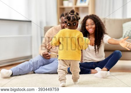 family, parenthood and people concept - happy african american mother and father playing with baby daughter at home