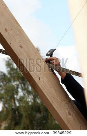 Man Nailing A Lath To A Roof Rafter
