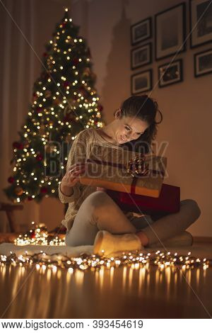 Beautiful Young Woman Celebrating Christmas At Home, Having Fun While Opening Christmas Presents