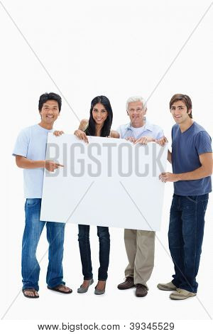 Smiling people holding and showing a big sign against white background