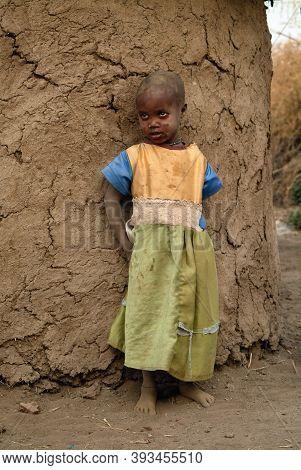 Masai Mara, Kenya - Aug 23, 2010: Little Unidentified Kenyan Girl From Masai Tribe Dressed With Simp