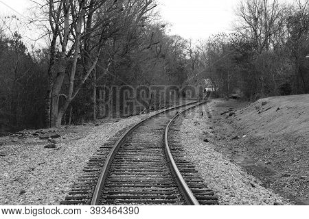A Single Spooky Train Tracks Leading Into The Distance In Black And White