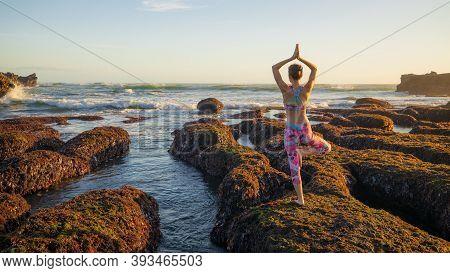 Vrikshasana, Tree Pose. Balancing Asana. Caucasian Woman Standing On Big Stone During Low Tide. Yoga