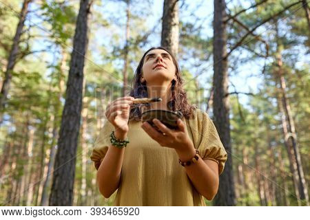 occult science and supernatural concept - young woman or witch with smoking palo santo stick performing magic ritual in forest