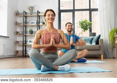 fitness, people and healthy lifestyle concept - happy smiling man and woman meditating in yoga lotus pose at home