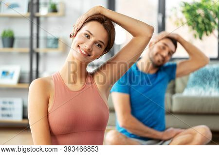 sport, fitness, lifestyle and people concept - smiling man and woman stretching neck at home