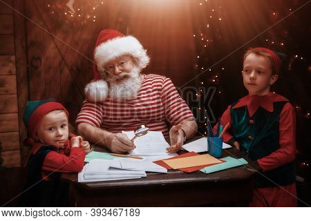 Santa Claus and little elves are sorting mail, reading letters from children. House, workshop of Santa Claus.