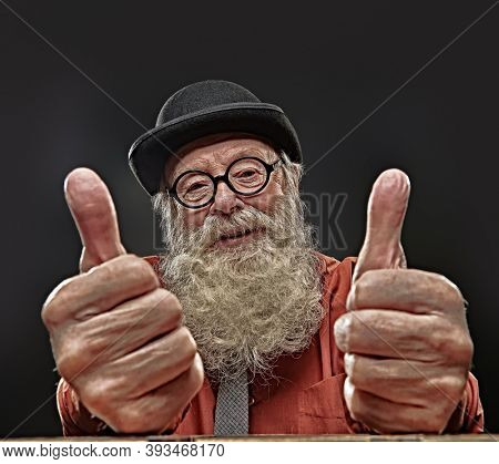 Old age. Portrait of a positive old-fashioned old man with a white beard in a bowler hat and round glasses showing thumbs and smiling. Black background.